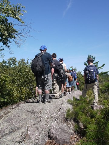 Hikers lined up on outcrop, Jeremy Glick Trail, Abram S. Hewitt State Park, NJ